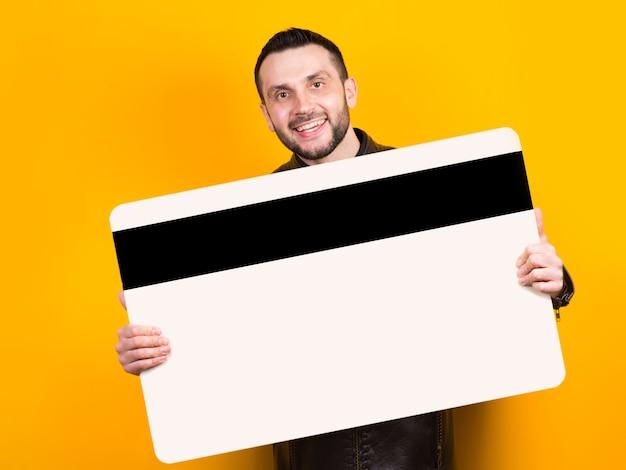 Cheerful man tenant une énorme carte bancaire dans ses mains