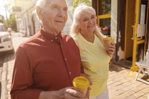 Cheerful mature paire d'amoureux avec des tasses marche ensemble le long de la rue de la ville