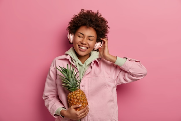 Cheerful millennial woman écoute de la musique et bénéficie d'un excellent son dans les écouteurs