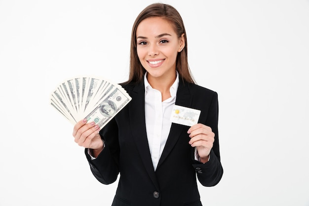 Cheerful pretty businesswoman holding argent et carte de crédit