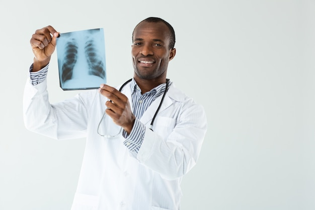 Cheerful professional doc holding x-ray scan wgile debout contre le mur blanc