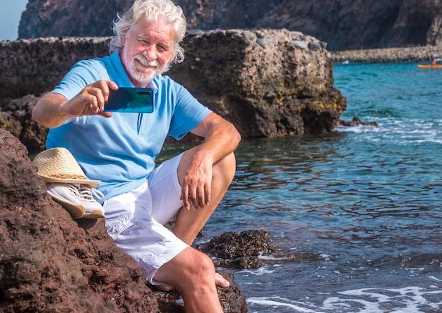 Cheerful senior man jambes nues à l'aide d'un téléphone intelligent pour un selfie assis sur les rochers près de l'eau