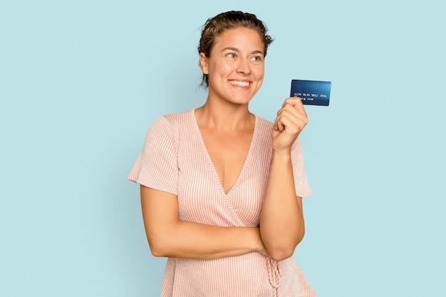 Cheerful shopaholic woman holding paiement sans numéraire par carte de crédit