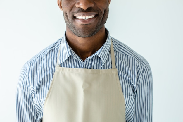 Cheerful smiling barista afro-américain debout contre le mur blanc