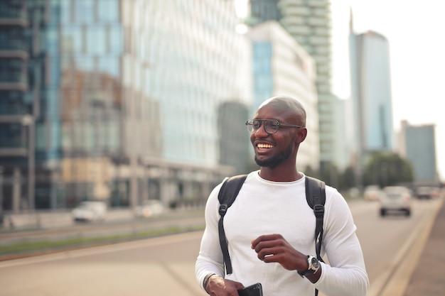 Cheerful smiling male africain avec des lunettes portant un t-shirt blanc et un sac à dos à l'extérieur