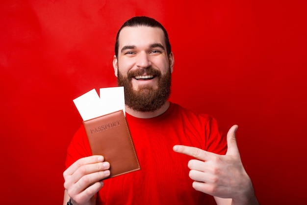Cheerful smiling man avec barbe pointant sur le passeport et les billets sur le mur rouge