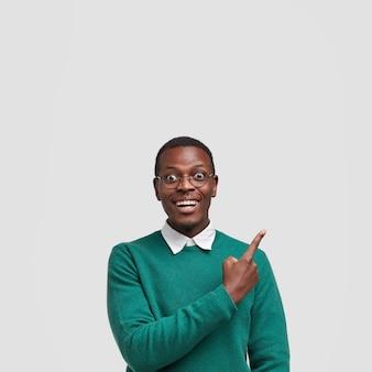 Cheerful smiling points masculins à la peau sombre avec l'index vers le haut, heureux de démontrer l'espace libre pour votre promotion