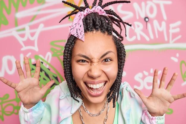 Cheerful teenage girl has fun sourires soulève largement les paumes regarde volontiers l'appareil photo heureux de faire des graffitis créatifs sur le mur de la rue appartient à la culture des jeunes