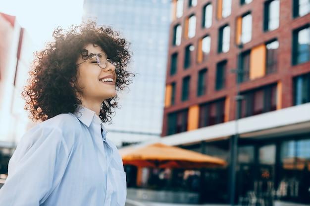 Cheerful woman aux cheveux bouclés acclame à l'extérieur tout en portant une chemise blanche et des lunettes