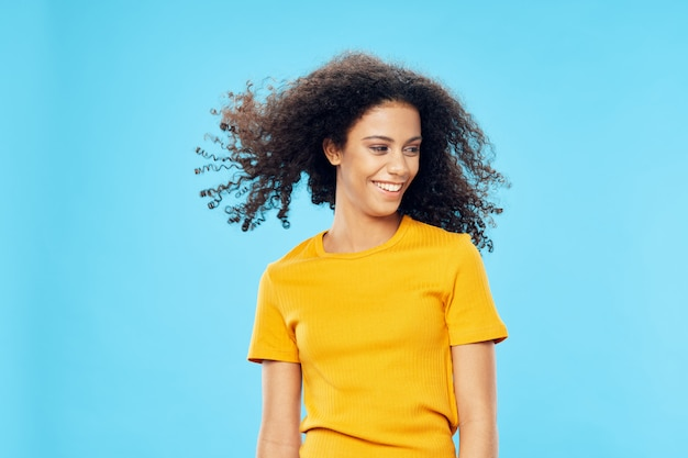 Cheerful woman aux cheveux bouclés coiffure afro en t-shirt jaune look attrayant sourire et