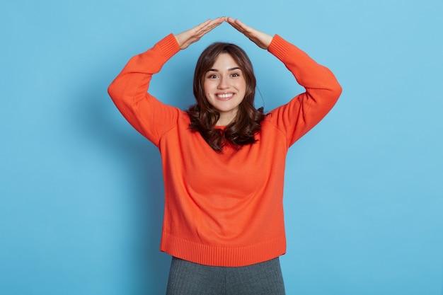 Cheerful woman aux cheveux noirs en pull orange faisant le toit des mains au-dessus de la tête