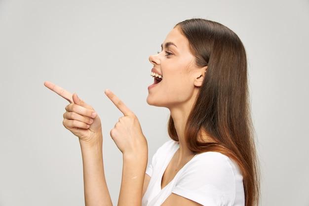 Cheerful woman avec la bouche ouverte montre ses doigts vers