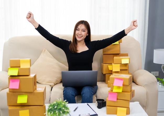 Cheerful woman entrepreneur travaillant avec un ordinateur portable et succès de la vente de produits en ligne au bureau à domicile