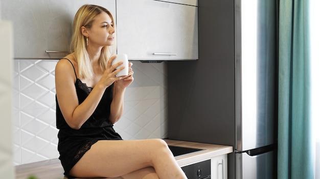 Cheerful woman est assis sur un comptoir dans une cuisine moderne blanche