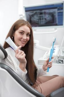Cheerful woman holding brosse à dents et dentifrice, assis dans un fauteuil dentaire