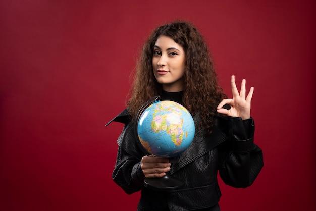 Cheerful woman holding globe et donnant le signe ok.