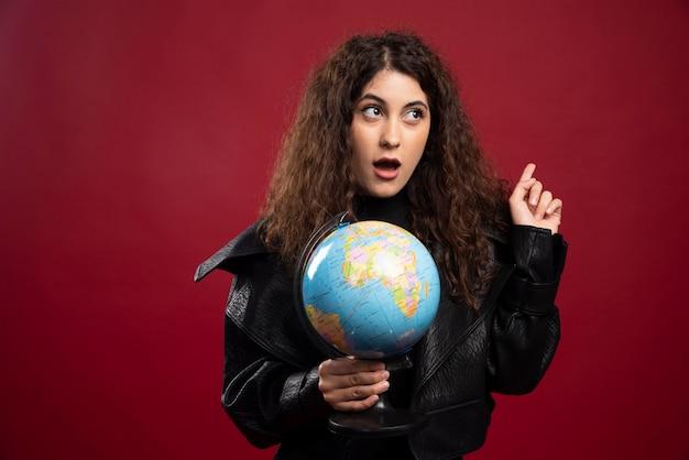 Cheerful woman holding globe.
