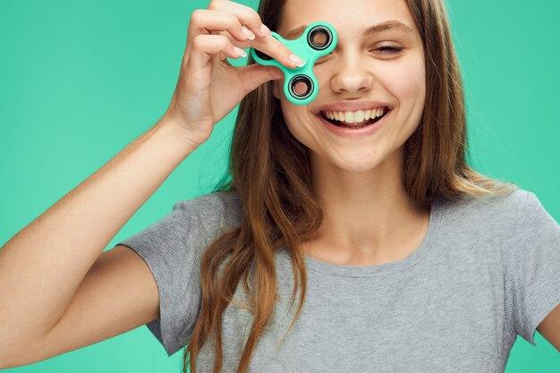 Cheerful woman holding a spinner dans sa main fond vert