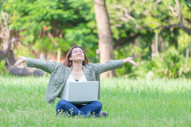 Cheerful woman ouvert assis sur l'herbe