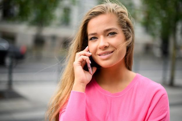 Cheerful woman parler au téléphone dans la rue