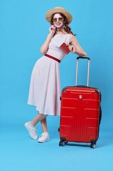 Cheerful woman passager bagages aéroport vol fond bleu