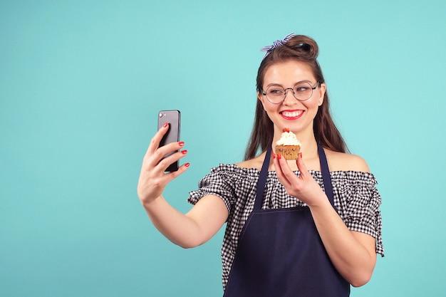 Cheerful woman pâtissier fait un selfie avec un petit gâteau à la main