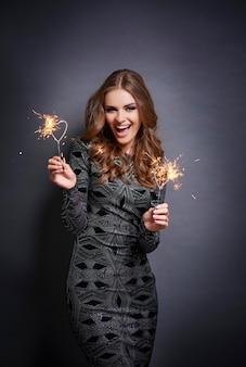 Cheerful woman posant avec sparkler