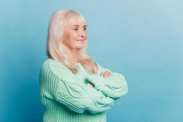 Cheerful woman stand avec bras croisés sur fond bleu