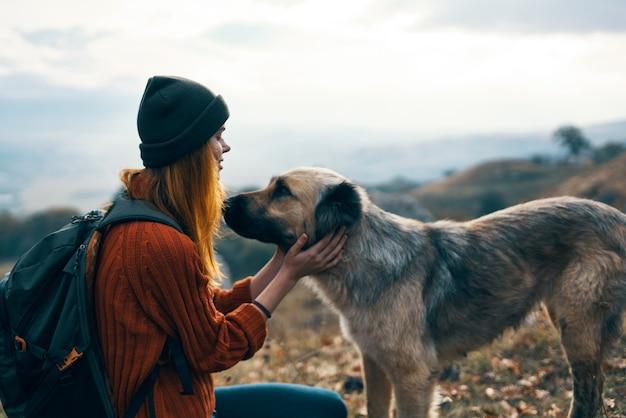 Cheerful woman touriste à côté du chien jeux d'amitié amusants
