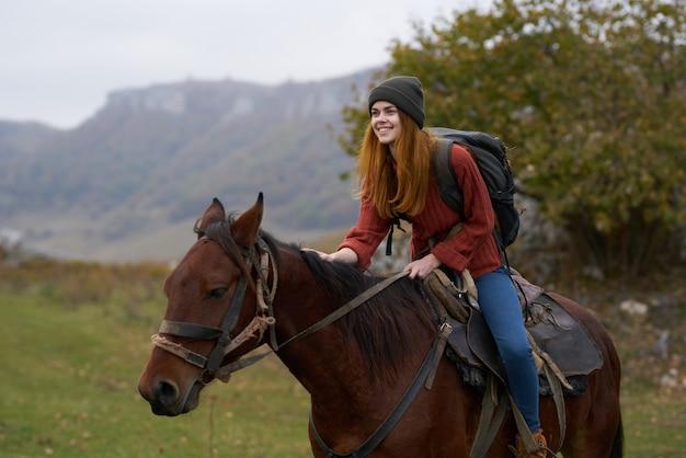 Cheerful woman touriste monté sur un cheval nature montagnes joie