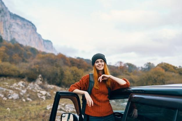 Cheerful woman touriste près de voiture voyage vacances amusement