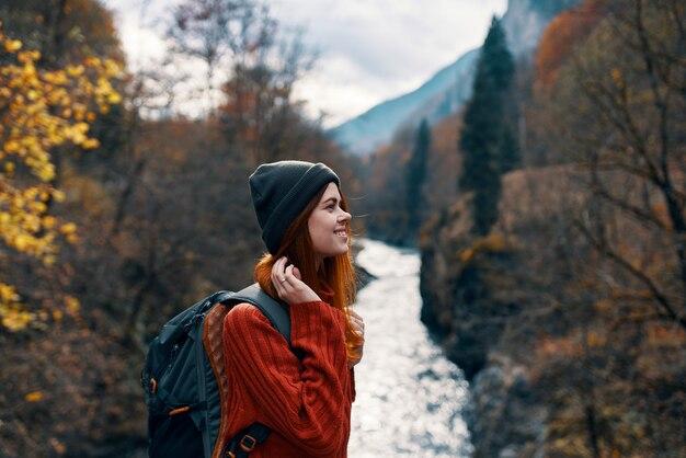 Cheerful woman touriste de toute la loi admire la nature de la rivière de montagne