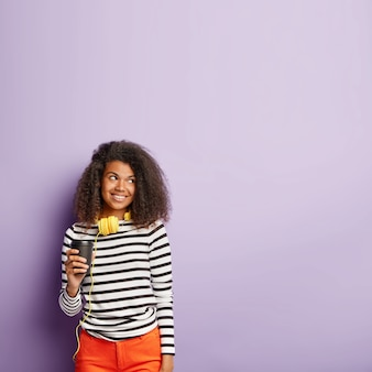 Cheerful woman with afro coiffure boit du café ou du thé à emporter