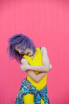 Cheerful woman with afro hair dancing avec une robe jaune cool sur un mur rose