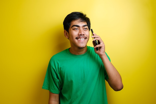 Cheerful young asian man sur appel sur fond jaune
