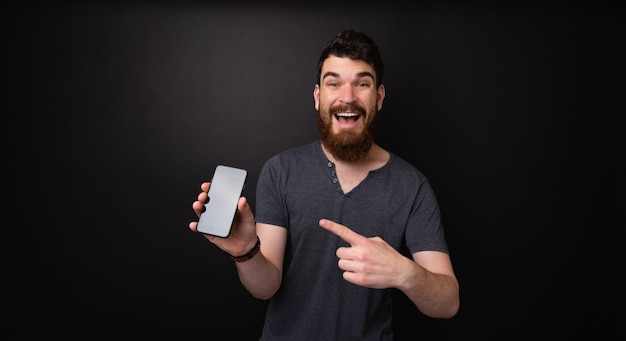 Cheerful young barbu pointant sur mobile debout sur fond sombre isolé