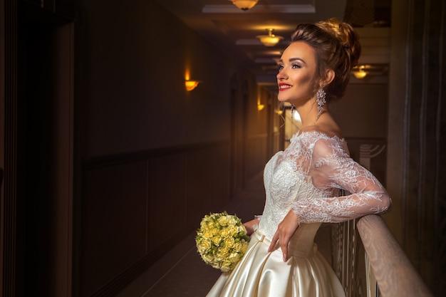 Cheerful young blonde bride smiling et regardant de côté en robe de mariée