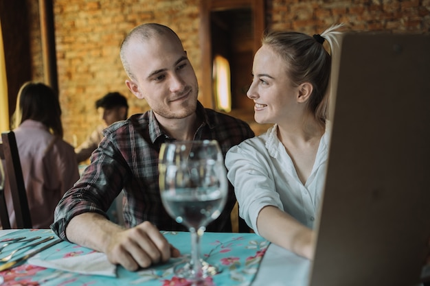 Cheerful young caucasian couple lisant le menu.