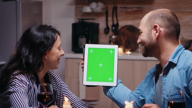 Cheerful young couple using green mock-up screen digital tablet computer. mari et femme regardant l'affichage de la clé chroma du modèle d'écran vert assis à la table dans la cuisine pendant le dîner.