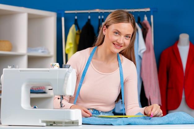 Cheerful young couturière assis à table de travail avec machine à coudre dans son bureau