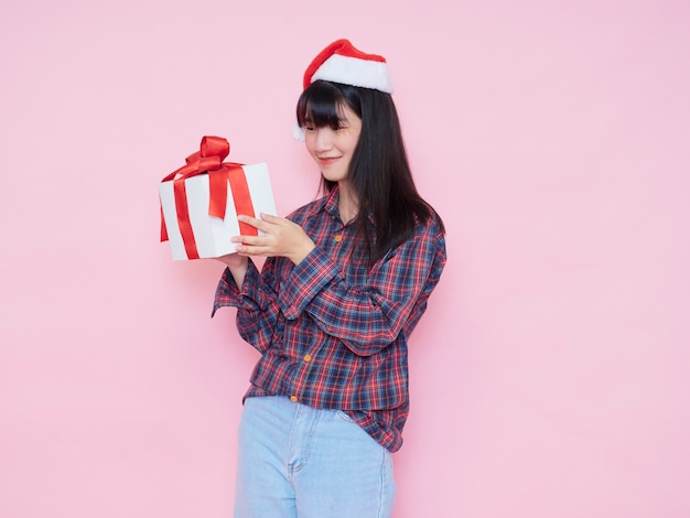Cheerful young girl wearing santa hat en chemise à carreaux avec holding gift box sur fond rose