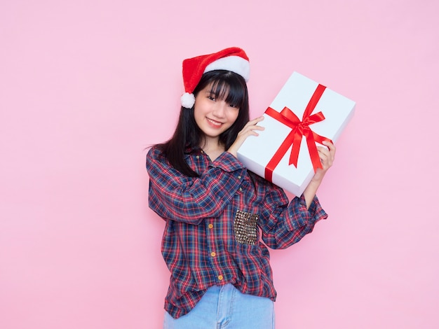 Cheerful young girl wearing santa hat en chemise à carreaux avec holding gift box on pink