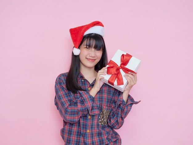 Cheerful young girl wearing santa hat avec tenant des coffrets cadeaux sur mur rose