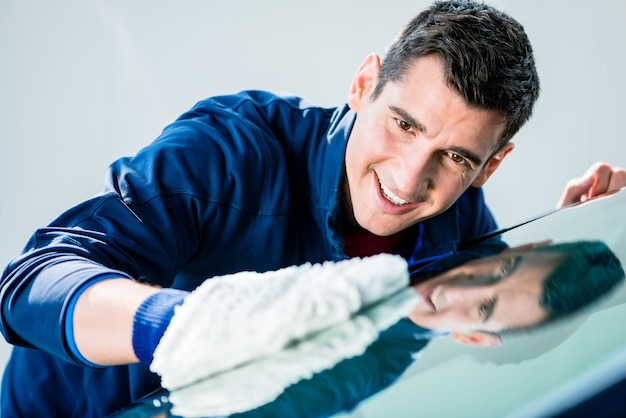 Cheerful young male worker polissage voiture avec gant en microfibre douce blanche au lavage automatique