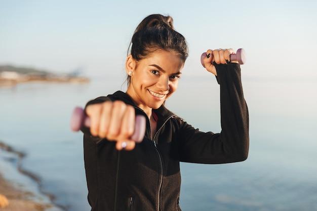 Cheerful young sportsgirl faisant des exercices avec de petits haltères