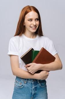 Cheerful young woman college student holding books et à l'écart sur fond isolé