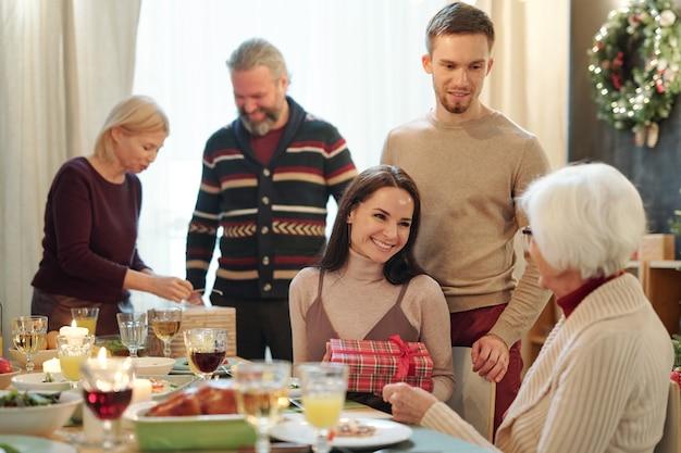 Cheerful young woman holding coffret cadeau tout en faisant un cadeau de noël à sa grand-mère par table de fête servi