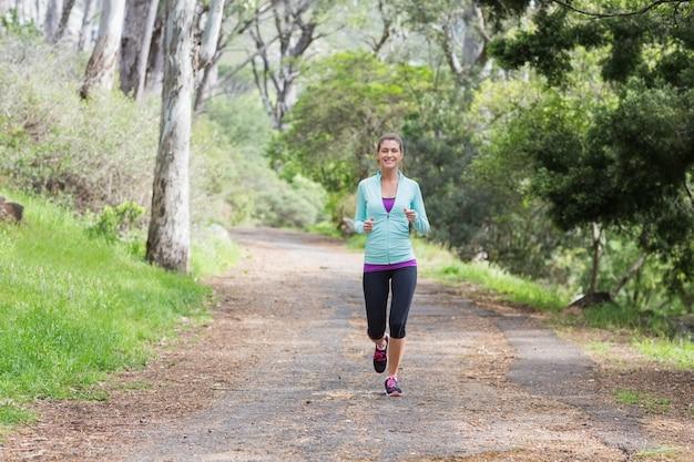 Cheerful young woman jogging dans la forêt