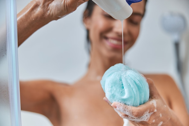 Cheerful young woman pouring gel douche sur bain loofah