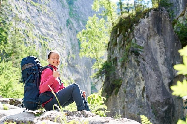 Cheerful young woman smiling joyeusement montrant les pouces vers le haut assis sur le dessus d'un rocher